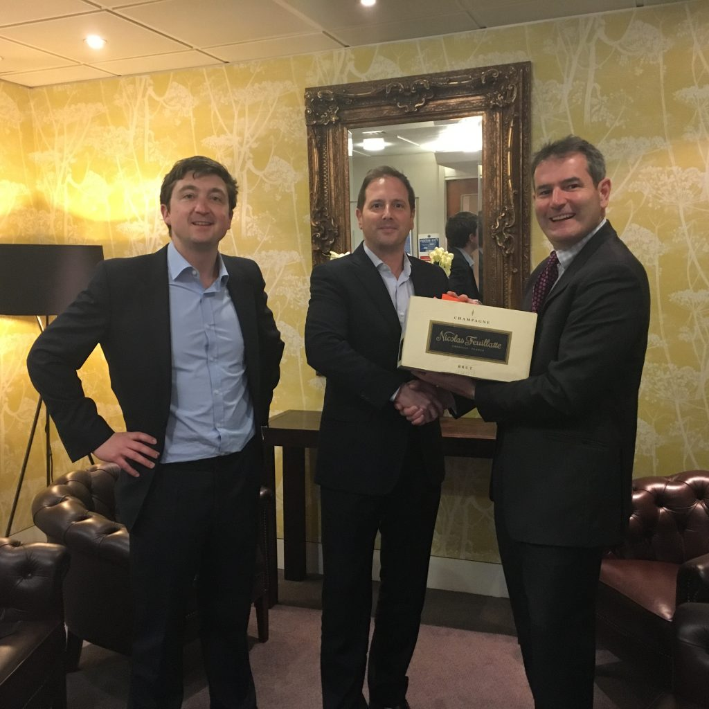 Christopher Stiegeler (centre) receives his case of champagne from Saul Shanagher (r) and Andy Prior (l)
