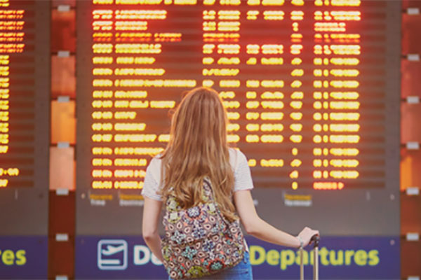 A young woman traveller is looking up at the departure board in an airport
