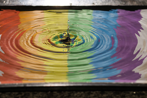 A water droplet hitting a pool of water, which is coloured in stripes, one for each colour of the rainbow