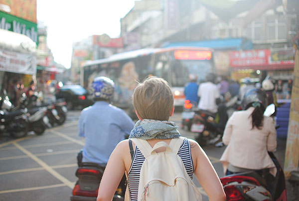 A woman traveller is stood on a busy road